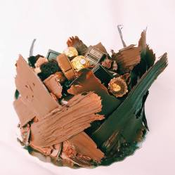 """8"""" 3 layer chocolate kake with chocolate buttercream. Topped with dark chocolate ganache, and an assortment of decadent chocolates, wrapped in hand painted chocolate pieces. $80.00"""