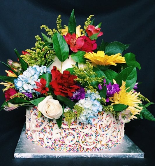 """12"""" 3 layer choco kake & 8"""" 3 layer vanilla kake covered in vanilla buttercream, fondant & sprinkles, topped with an assortment of flowers. $300.00"""