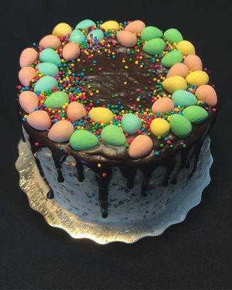 Gluten free vanilla bean mini egg kake filled and covered w/ mini egg buttercream, dark chocolate ganache, mini eggs & sprinkles.